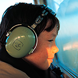 Boy in aviation headset looking out aircraft window